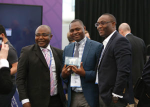 Sean Agbor-Enoh, MD, PhD (center) celebrates his BEAR Cage Award with two colleagues